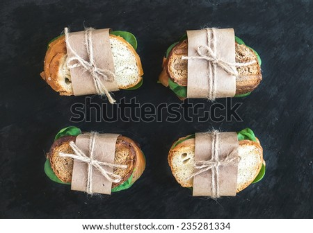 Chicken and spinach sandwiches wrapped in craft paper over a dark stone background. Top view - stock photo