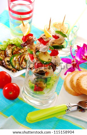 chicken and vegetable skewers served in glass with grilled aubergine and zucchini salad - stock photo