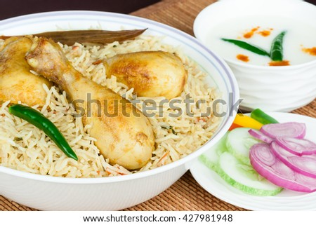 Chicken biryani closeup - Extreme closeup view of delicious Indian chicken biryani with garnish, served with raita and colorful salad. Traditional presentation. Shallow DOF. - stock photo