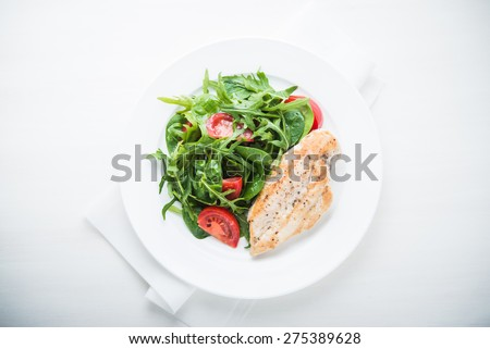 Chicken breast and fresh salad with tomato and greens (spinach, arugula) top view on white wooden background. Healthy food. - stock photo