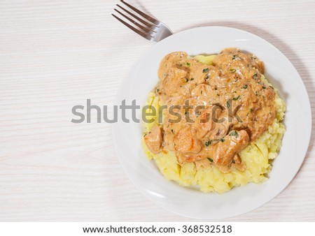 chicken breast in a creamy sauce with mashed potatoes