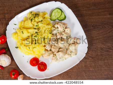 chicken breast in a creamy sauce with mashed potatoes in a plate on wooden table