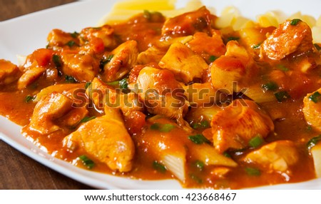 chicken breast in tomato sauce with penne pasta in a plate on wooden table
