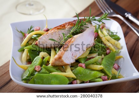 Chicken breast on various beans and ham
