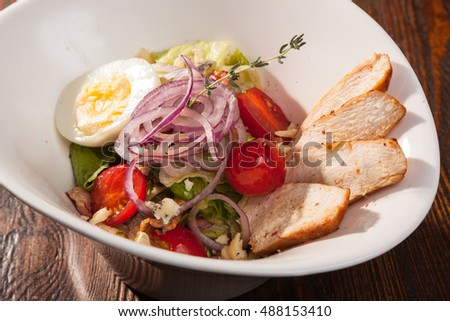 chicken breast salad with cherry tomatoes and egg in white plate