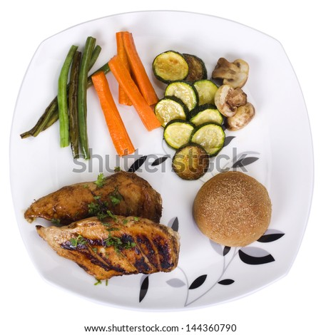 Chicken breast with bread and vegetables on a plate - stock photo