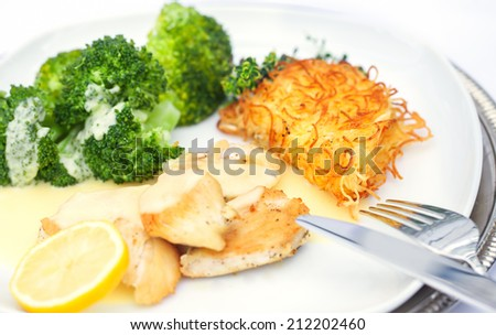 Chicken breast with broccoli and fried noodles on a plate on white background - stock photo
