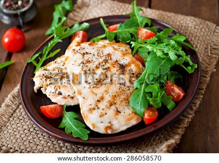 Chicken breast with fresh salad - arugula and tomato - stock photo