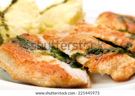 Chicken breast with mashed potatoes and pesto.