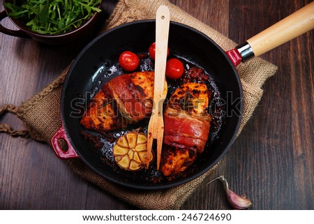 chicken breast wrapped in parma ham with cherry tomatoes, garlic and herbs in cast iron pan - stock photo