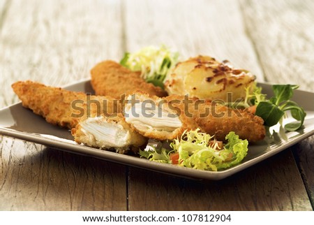 Chicken breasts coated in breadcrumbs - stock photo