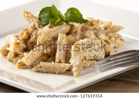 chicken breasts cut on small pieces with whole grain penne pasta, alfredo sauce and grated parmesan cheese - oven baked Italian casserole dish served on white plate with fork and brown napkin on white - stock photo