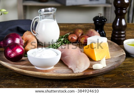Chicken breasts with fresh healthy  vegetables, cheese, oil and spices.  Raw products on the wooden background - stock photo