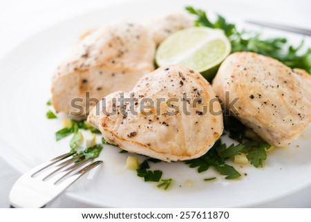 Chicken breasts with parsley and citrus on white background close up. Healthy food. - stock photo