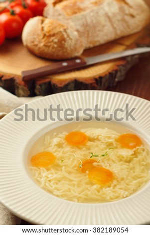 Chicken broth with noodles and carrots in a white plate on a rustic wooden background. Shallow focus