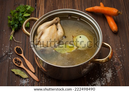 chicken broth with vegetables and spices in a saucepan  - stock photo