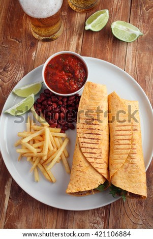 Chicken burritos with French fries, red bean, salsa sauce, and beer - stock photo