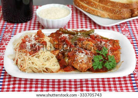 Chicken cacciatore stew with spaghetti on the side and a side of Italian bread.