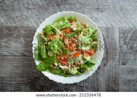 Chicken caesar salad on wooden table - stock photo
