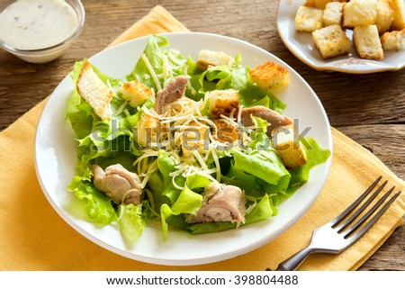 Chicken caesar salad with cheese and croutons over rustic wooden background close up - stock photo