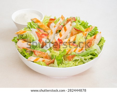 Chicken caesar salad with dressing - stock photo