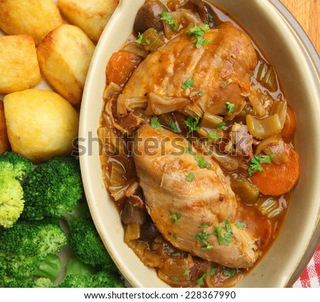 Chicken casserole served with roast potatoes and broccoli - stock photo