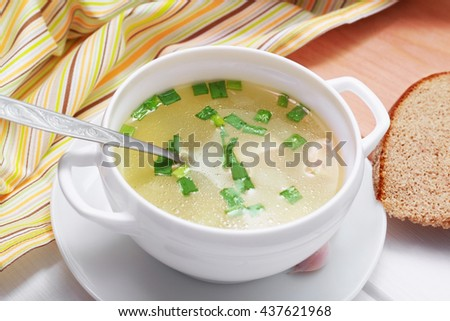 Chicken clear soup in white bowl and bread on the table