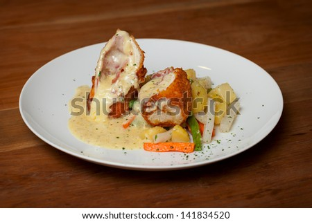 Chicken Cordon Bleu with boiled vegetables close up - stock photo