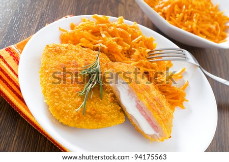 Chicken cordon bleu with grated carrots. - stock photo