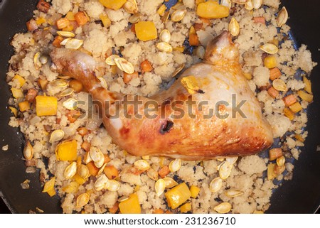 Chicken, couscous. pumpkin, seeds and carrot. On a frying pan - stock photo