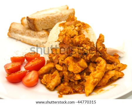 Chicken curry dish with tomato and bread on side