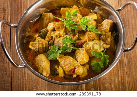 Chicken curry in  balti dish on a rustic wooden table. Selective focus
