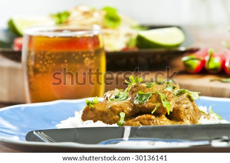 Chicken curry served  with rice and garnished with cilantro leaves - stock photo