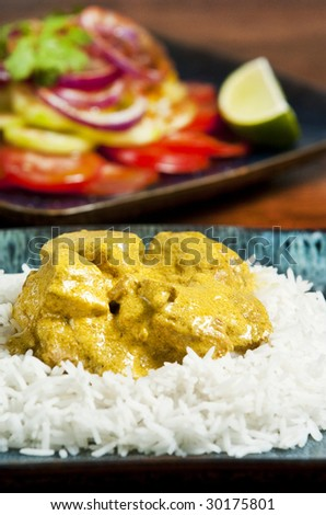 Chicken curry served  with rice and garnished with cilantro leaves