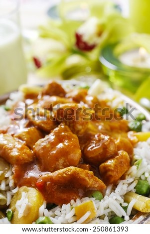 Chicken curry with basmati rice and green peas, dish popular in India.