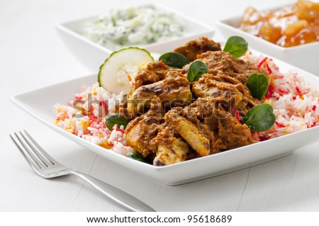 Chicken curry with pilau rice served on plate with fork on table. Cucumber raita and mango chutney behind. - stock photo