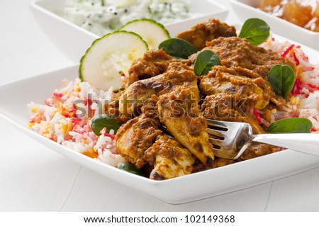 Chicken curry with pilau rice served on plate with fork used in food. Cucumber raita and mango chutney behind. - stock photo