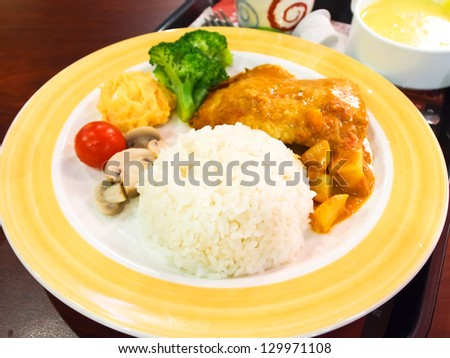 Chicken curry with rice on yellow plate - stock photo