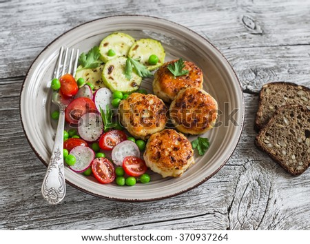 Chicken cutlets,  grilled zucchini  and fresh vegetable salad on rustic light wood background - stock photo