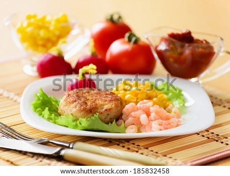 Chicken cutlets with canned corn and peeled shrimp. Served with fresh vegetables. - stock photo