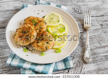 chicken cutlets with lemon and herbs on a white plate on a  wooden background - stock photo