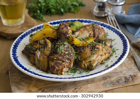 Chicken drumsticks and thighs with peppers, lemon and chilli - stock photo