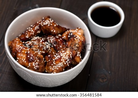 Chicken drumsticks in a sweet and sour sauce in Thai with sesame seeds on a plate closeup - stock photo