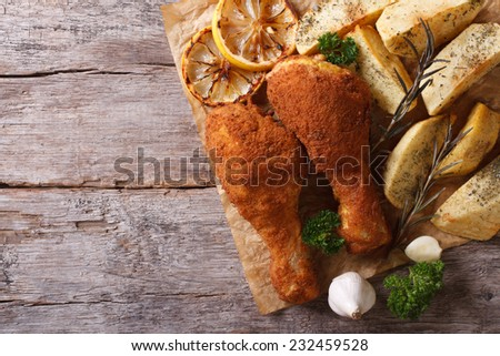 Chicken drumsticks in breadcrumbs with potatoes close-up. horizontal view from above - stock photo