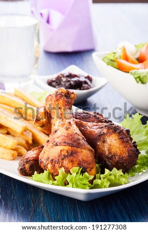 Chicken drumsticks with chips. Selective focus
