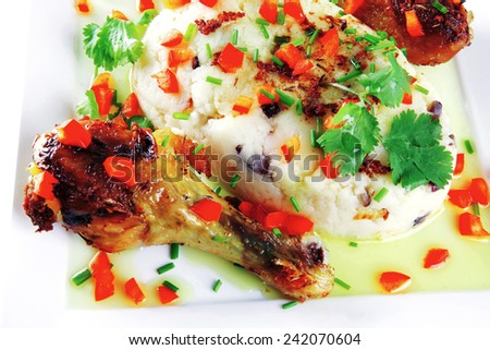 chicken drumsticks with mash on white plate - stock photo