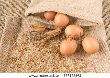 chicken egg and dry lily flower seed on  sackcloth
