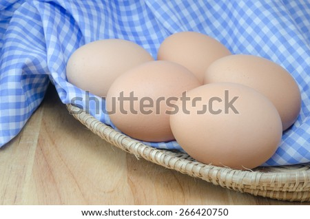 Chicken egg in a basket with blue cloth on wodden table