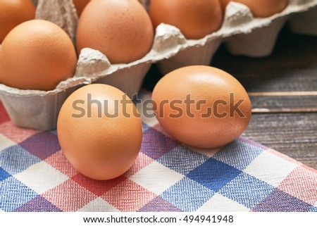 Chicken eggs and pulp egg carton on table