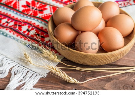 Chicken eggs in a wooden bowl on rushnyk